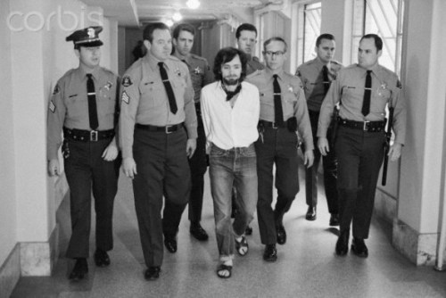 25 Jan 1971, Los Angeles, California, USA --- Seven deputies escort Charles Manson from the courtroom after he and three followers were found guilty of seven murders in the Tate-LaBianca slayings. --- Image by © Bettmann/CORBIS